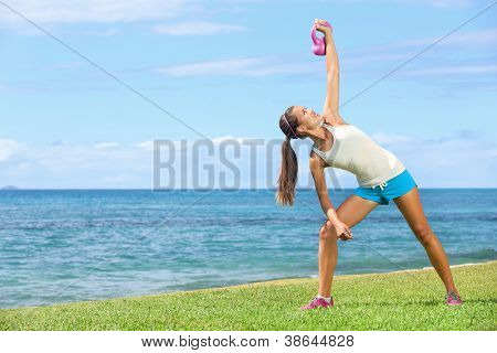 exercise woman using kettlebell in fitness strength training workout outside on grass by the ocean. Beautiful young fit instructor and fitness model.