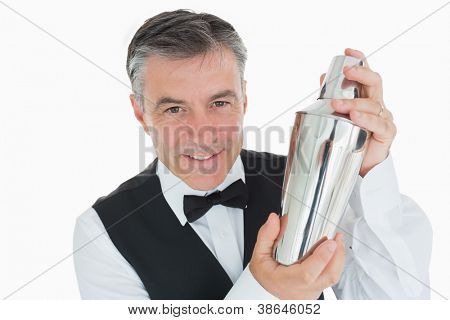 Smiling waiter in suit shaking drink in cocktail shaker