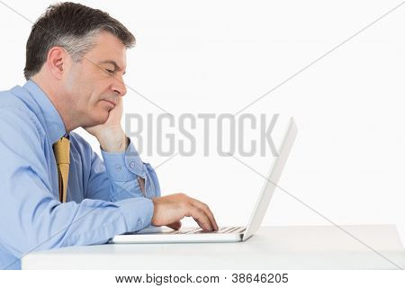 Tired man writing on his computer on his desk in a white background