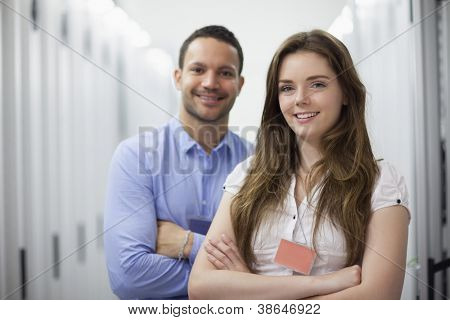 Smiling technicians with arms crossed in data center