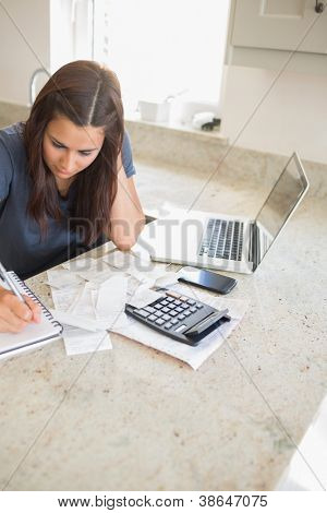 Woman calculating finances in kitchen