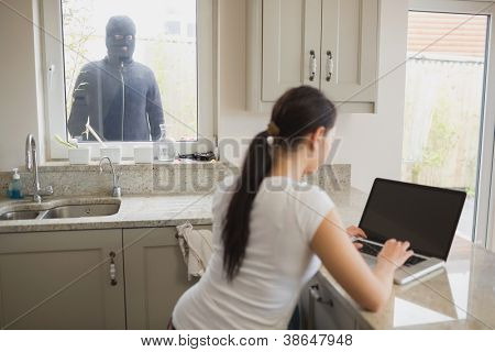 Woman on laptop in kitchen being observed by burglar through window