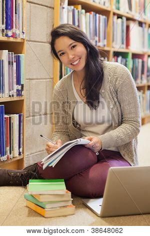 Smiling student working with laptop on library floor beside book shelf