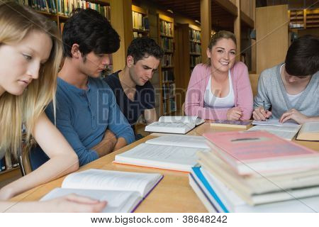Students in the library studying together around table with one girl looking up and smiling