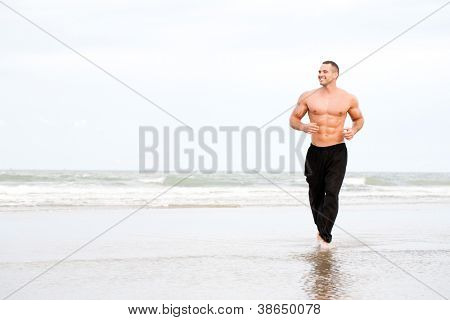Young handsome muscular man running on the beach