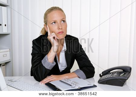 a pensive businesswoman sitting at her desk in an office