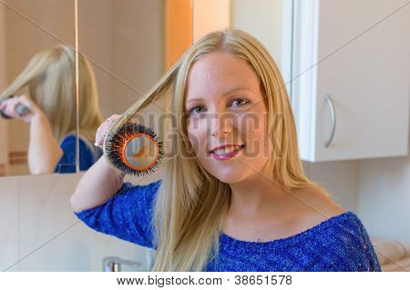 a young woman is familiar with a brush her long blonde hair in the bathroom
