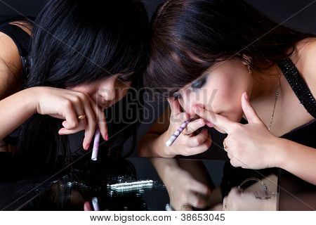 girls are sniffing cocaine (imitation). isolated on a black background