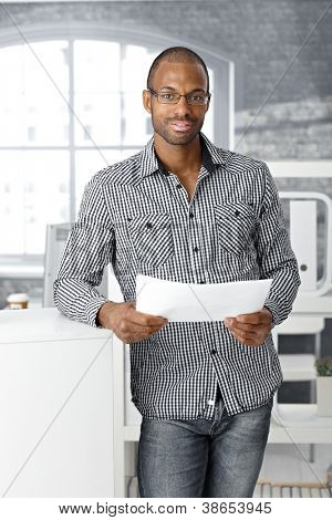Portrait of ethnic office worker smiling, standing with document handheld, looking at camera.