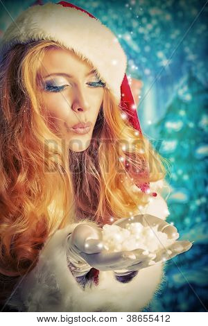 Beautiful young woman in Santa Claus clothes blowing snow.