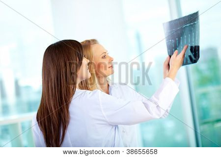 Portrait of young doctor commenting x-ray exam results to her colleague