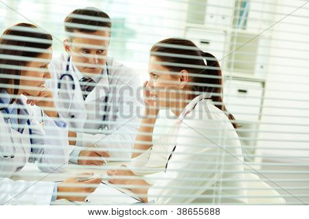 Portrait of confident practitioners consulting patient in medical office