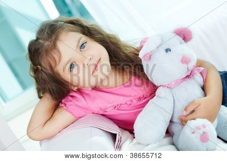 Portrait of lovely girl with teddybear sitting on sofa and ooking at camera