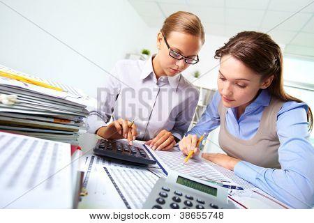 Retrato de duas mulheres trabalhando com documentos e calculadora no escritório