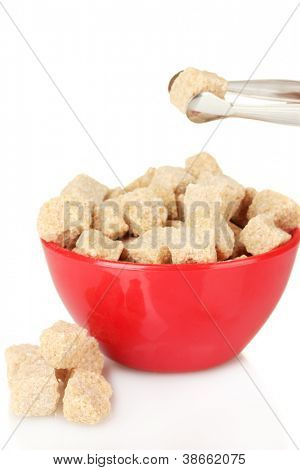 brown cane sugar cubes in bowl with sugar-tongs on white background