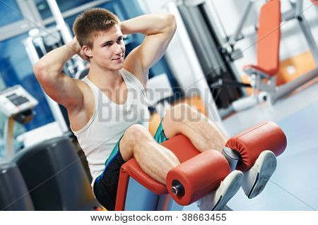 bodybuilder man at abdominal crunch muscles exercises during training in fitness gym