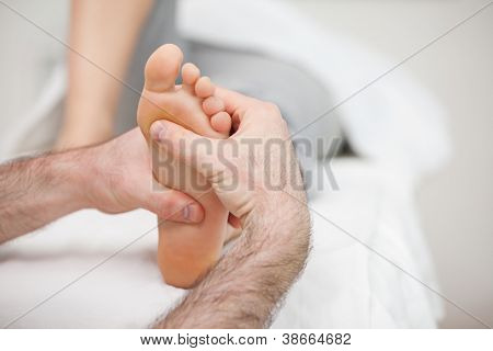 Man using his two hands to massage a foot in a room