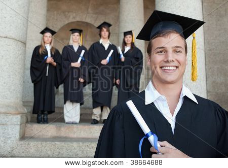 Close-up of a happy graduate smiling with her friends in background in front of the university