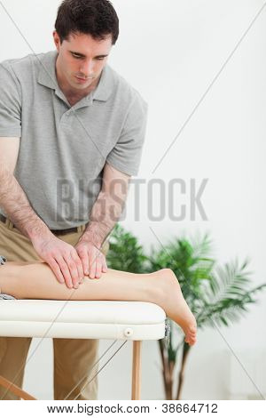 Brunette masseur massaging the leg of a woman in a room
