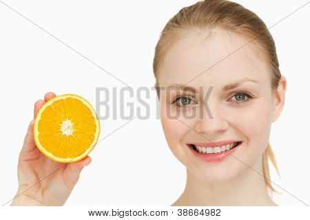 Close up of a cheerful woman presenting an orange against white background