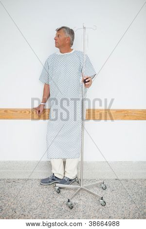 Man is standing against the wall of the corridor in the hospital with his IV drip