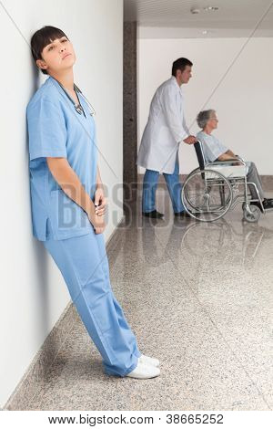 Tired nurse leaning against wall while doctor pushes patient in wheelchair
