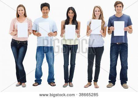 Pessoas em jeans segurando cinco sinais contra fundo branco