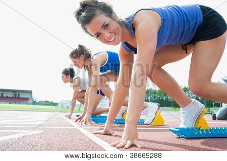 Happy woman at starting blocks on track field