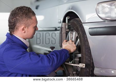 Concentrated mechanic repairing a car wheel in a garage