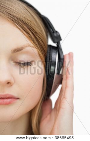 Close up of a woman with closed eyes listening music against a white background