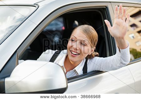 friendly young woman sitting in the car and waving her hand