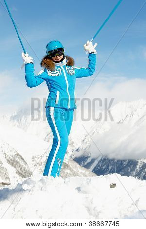 Young woman in blue ski suit stands  on top of hill rising up her hands with ski poles overhead, snowy mountains and blue sky on background.
