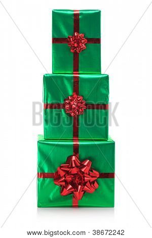 Three gift wrapped presents in green wrapping paper with red bow and ribbon, isolated on a white background.