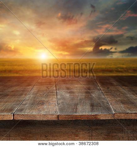 Mesa de madeira velha com cena rural no fundo