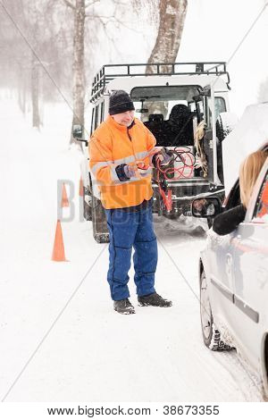 Man helping woman with broken car snow assistance winter mechanic