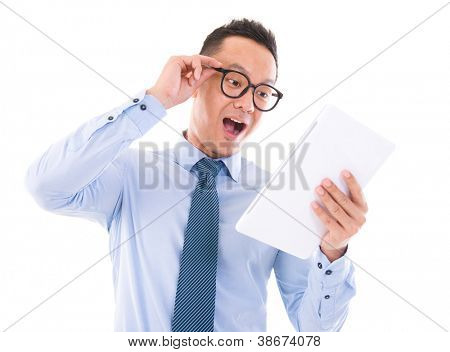 Surprise Asian business man looking at tablet computer, isolated over white background