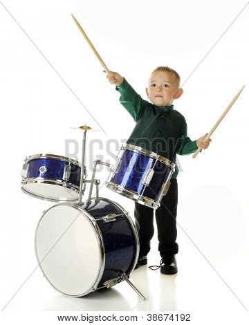 An adorable preschooler behind a drum set.  He's pretending to conduct an orchestra with his drum sticks.  On a white background.