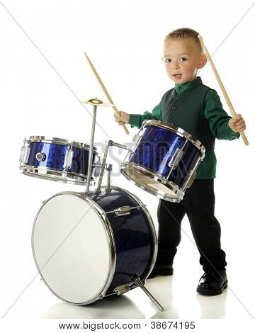 An adorable preschooler with drum sticks poised, waiting for a signal to begin his drum routine.  On a white background.