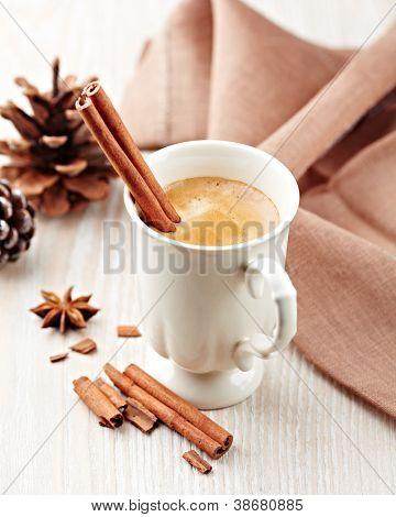 Mug of coffee with cinnamon and anise