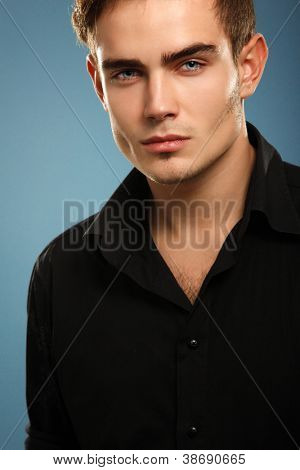 Handsome trendy young man in black shirt, portrait of sexy fashion boy looking right over dark blue background