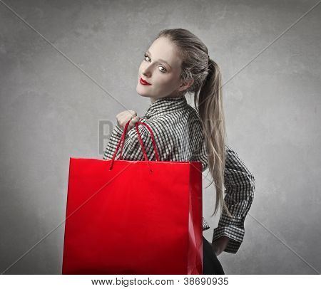 Beautiful blonde girl holding a red shopping bag