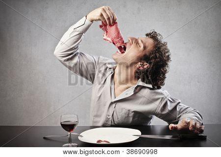Man gulping down a whole steak