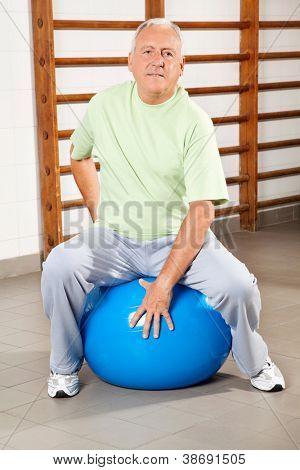 Full length of a senior man sitting on fitness ball at hospital gym
