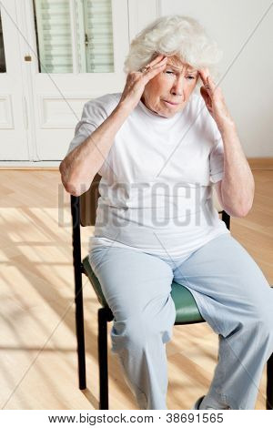 Senior woman sitting on chair suffering from headache