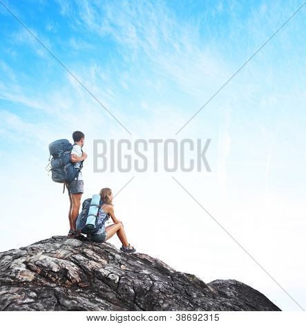 Two tourists with backpacks on top of a mountain