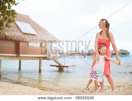 Mother and daughter at a beach in front of lagoon with overwater bungalows