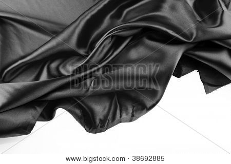 Closeup of folds in black silk fabric on white background