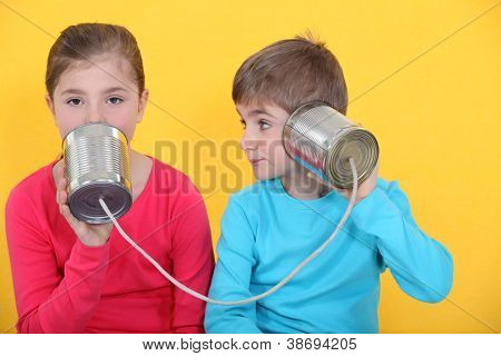 Brother and sister speaking through tin can and string