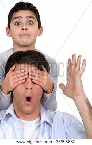 Boy covering his dad's eyes