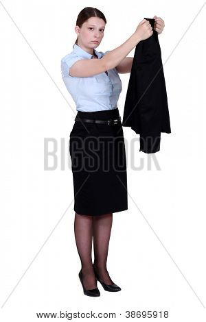 Unhappy businesswoman hanging her blazer up